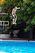 A young man diving off a board at Hotel Silvanetta Palace in Milazzo, Sicily July 2006