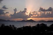 View of the sun setting over neighboring St. Thomas, Cruz Bay, St. John, U.S. Virgin Islands.