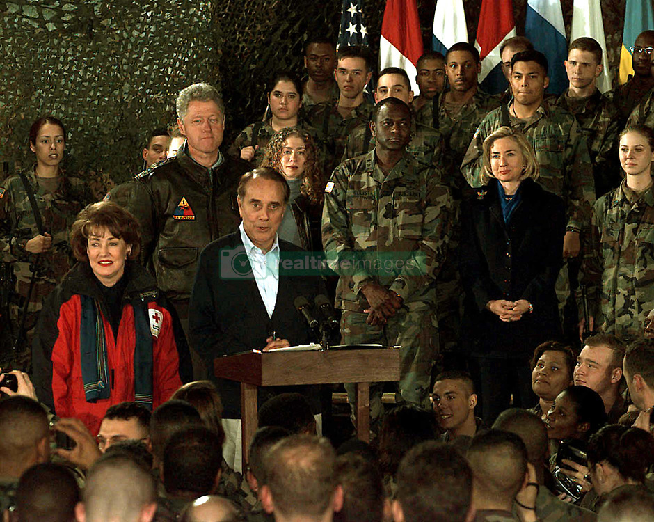 Former United States Senator Bob Dole (Republican of Kansas) talks to Task Force Eagle soldiers at the 21 Club, Eagle Base, Tuzla, Bosnia and Herzegovina, on December 22, 1997.  Dole and his wife Elizabeth (left) accompanied U.S. President Bill Clinton, first lady Hillary Rodham Clinton, and their daughter Chelsea for a holiday visit with the troops in Bosnia and Herzegovina. .Mandatory Credit: Johancharles V. Boers / U.S. Army via CNP        .