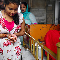 Girl receiving small sweets as blessing at Sitla Mandir temple in Amritsar.