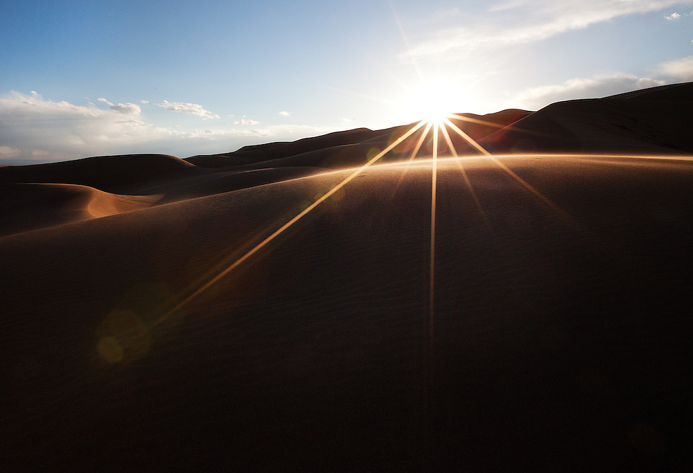 The setting sun dips behind the horizon at Great Sand Dunes National Park. High winds whipped up the sand, giving a soft focus to the arc of the foreground dune.