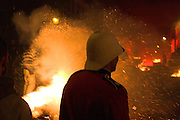 A bonfire society members dressed as a colonial soldier flinches from an exploding firework - Lewes, 5/11/05