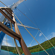 Ship mast construction in front of beautiful tropical coast area.