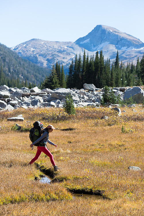 Woman crossing a small stream on a backpack trip in Oregon's Wallowa Mountains.