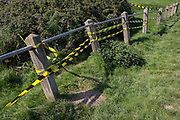 Yellow and black hazard tape stretches along the damaged barrier of a car park at Nailsea Lake, on 21st April 2019, in Nailsea, North Somerset, England.