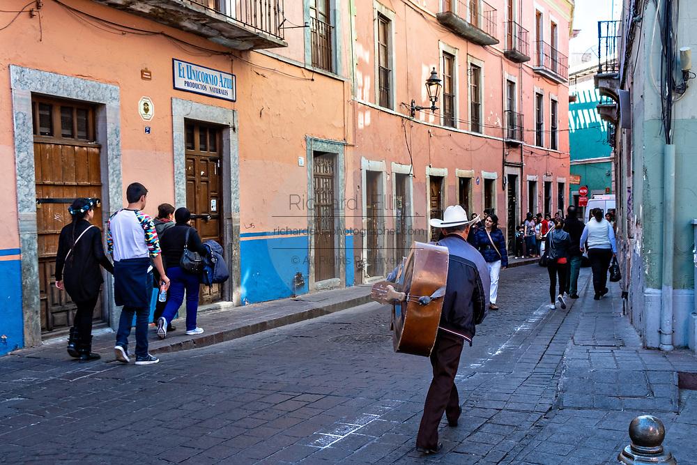 A musician carries a bass guitar down a cobblestone street in the historic center of Guanajuato City, Guanajuato, Mexico.