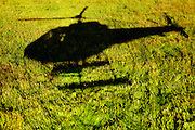 Shadow of helicopter on green grass as it is landing