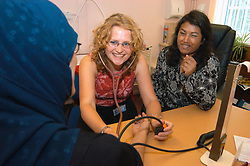 Medical student training with GP in doctors clinic; practising taking patients blood pressure; Yorkshire UK