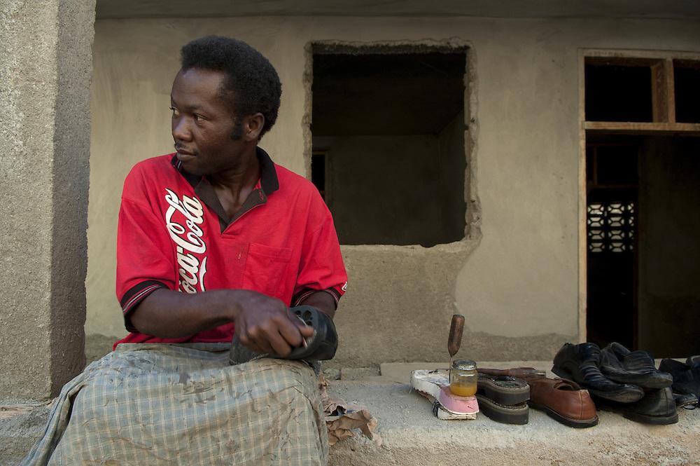 A shoemaker plies his trade in the streets. Cap Haitian, Haiti, January 26, 2008.