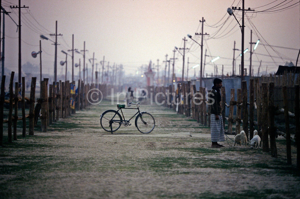 A bicycle is parked while a man walks two dogs at the Ardh Kumbh Mela 1995, Allahbad, India.The Kumbh Mela is a mass Hindu pilgrimage occuring four times every twelve years at four locations and is the largest gathering anywhere in the world.