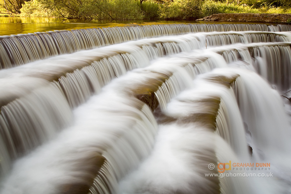 The River Wye flowing over Monsal Dale's impressive weir. Peak District, Derbyshire, England, UK.