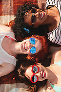 Three pretty young women laying down with sunglasses on.