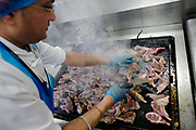 "A chef working for the world's largest independent provider of airline catering and provisioning services, Gate Gourmet, fries Welsh Lamb cutlets in the company's factory on the southern perimeter road at Heathrow Airport, West London. Gate Gourmet serve more than 200 million meals on 2 million airline flights a year to their 250-plus airline customers at more than 100 airport locations around the globe. Apart from creating the bespoke meals for an airline's culture and ethnic demands, that pack the pre-flight carts, deliver and load into the aircraft galleys and afterwards, they dispose of the waste and strip, wash and sterilize the equipment. From writer Alain de Botton's book project ""A Week at the Airport: A Heathrow Diary"" (2009)."