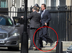 © Licensed to London News Pictures. 06/07/2016. London, UK. Prime Minister David Cameron appears to fly (ringed) across Downing Street as he leaves Number 10 for Parliament. Mr Cameron's left foot has accidentally lined up with the foot of one of his bodyguards to create the illusion that he is levitating. Photo credit: Peter Macdiarmid/LNP