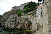 Buildings set in stone outcrop, beneath Fortress Lovrijenac (Fort of Saint Lawrence), Dubrovnik old town, Croatia