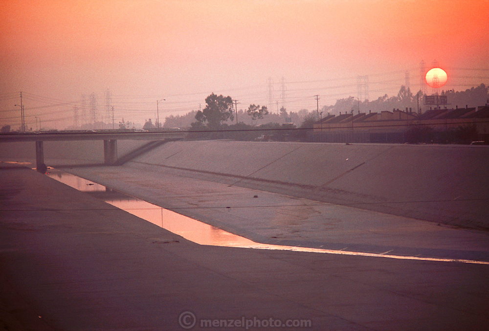 Los Angeles, California - Concrete-lined river with sun setting in smoggy sky behind power lines.