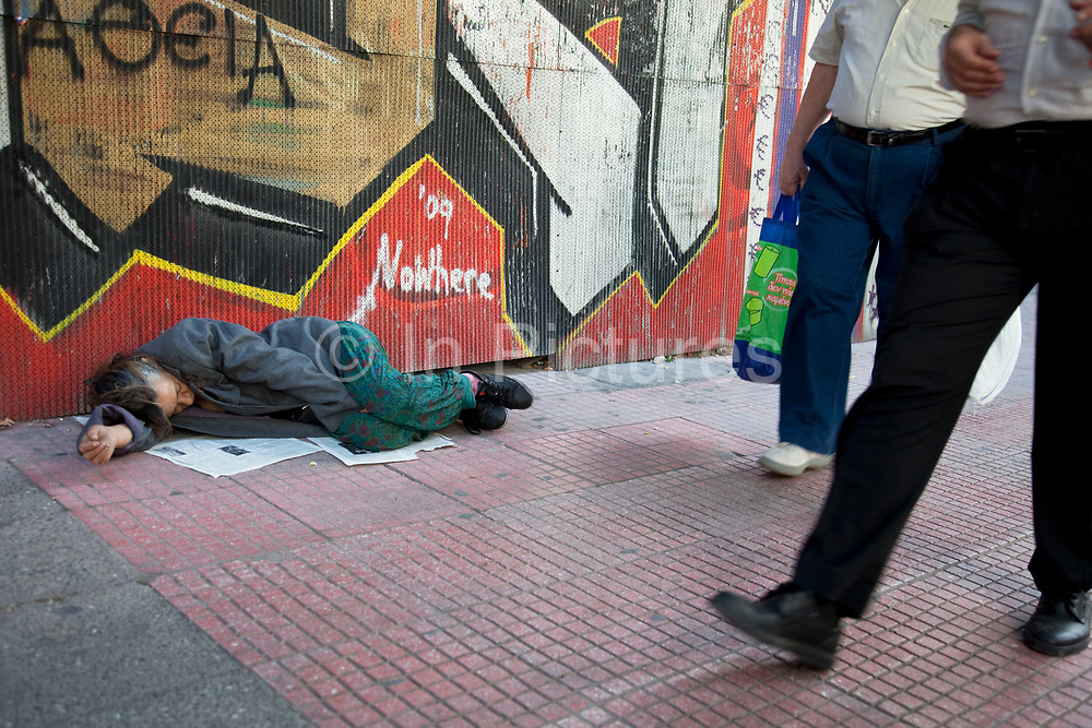 People walk past a woman sleeping on the streets against a graffitied wall. Disadvantaged people on the streets in the area of Omonia. In this area the amount of ill, disabled, badly injured, or sick people either begging or sleeping on the streets is staggering. The area has been taken over by drug dealers, homeless people, and prostitution. Athens is the capital and largest city of Greece. It dominates the Attica periphery and is one of the world's oldest cities, as its recorded history spans around 3,400 years. Classical Athens was a powerful city-state. A centre for the arts, learning and philosophy.