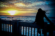 Young woman sitting on fence, looks over the sea at the setting sun