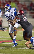 Kentucky Wildcats quarterback Morgan Newton (12) is brought down by Arkansas Razorbacks defensive tackle Jared Green (57) during the first half of a game at Donald W. Reynolds Razorback Stadium in Fayetteville, Ark., on Oct.. 13, 2012. Photo by Beth Hall