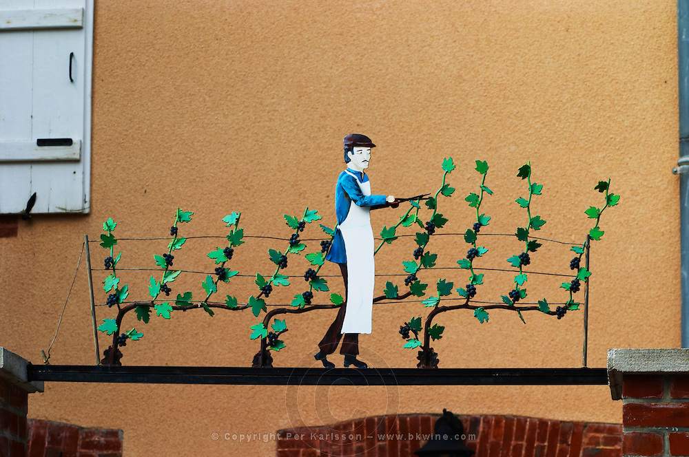 A wrought iron painted sign that illustrates the theme of champagne and wine production: A man pruning vines with leaves and grapes with a secateur, the village of Hautvillers in Vallee de la Marne, Champagne, Marne, Ardennes, France