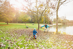 Little boy driving with his walking bicycle towards his mother in autumn scenery