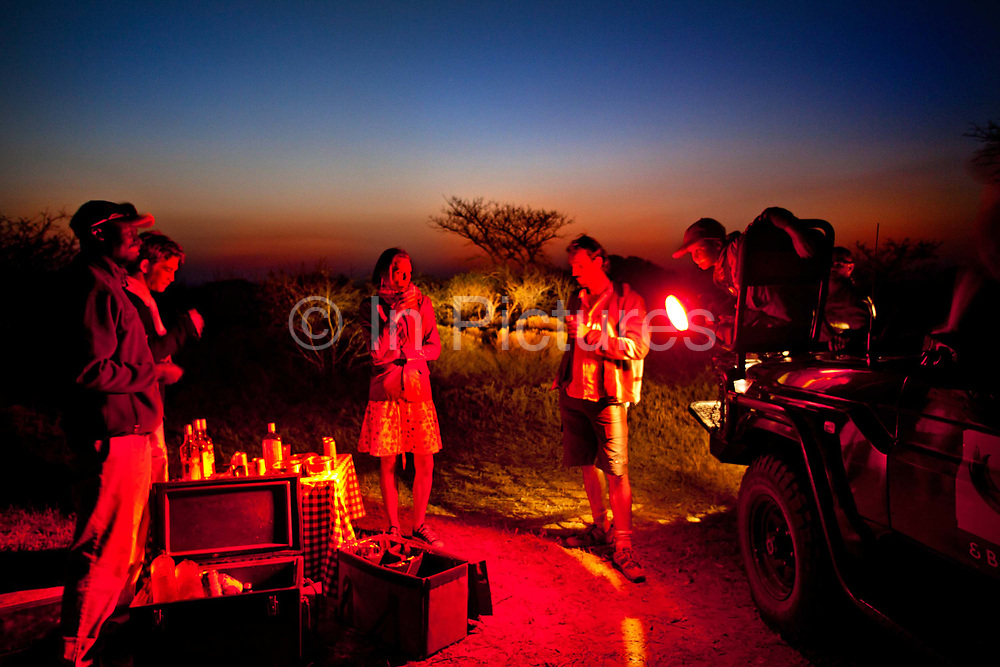 """Drinks on an evening game drive in the Phinda Game Reserve. <br /> <br /> Phinda Private Game Reserve encompasses an impressive 23 000 hectares (56 800 acres) of prime conservation land wilderness in KwaZulu-Natal, South Africa. Showcasing one of the continent's finest game viewing experiences. Phinda is described as """"Seven Worlds of Wonder"""", with its seven distinct habitats - a magnificent tapestry of woodland, grassland, wetland and forest, interspersed with mountain ranges, river courses, marshes and pans. Phinda is a wilderness sanctuary where intimate encounters, adventure and rare discoveries can be experienced firsthand."""