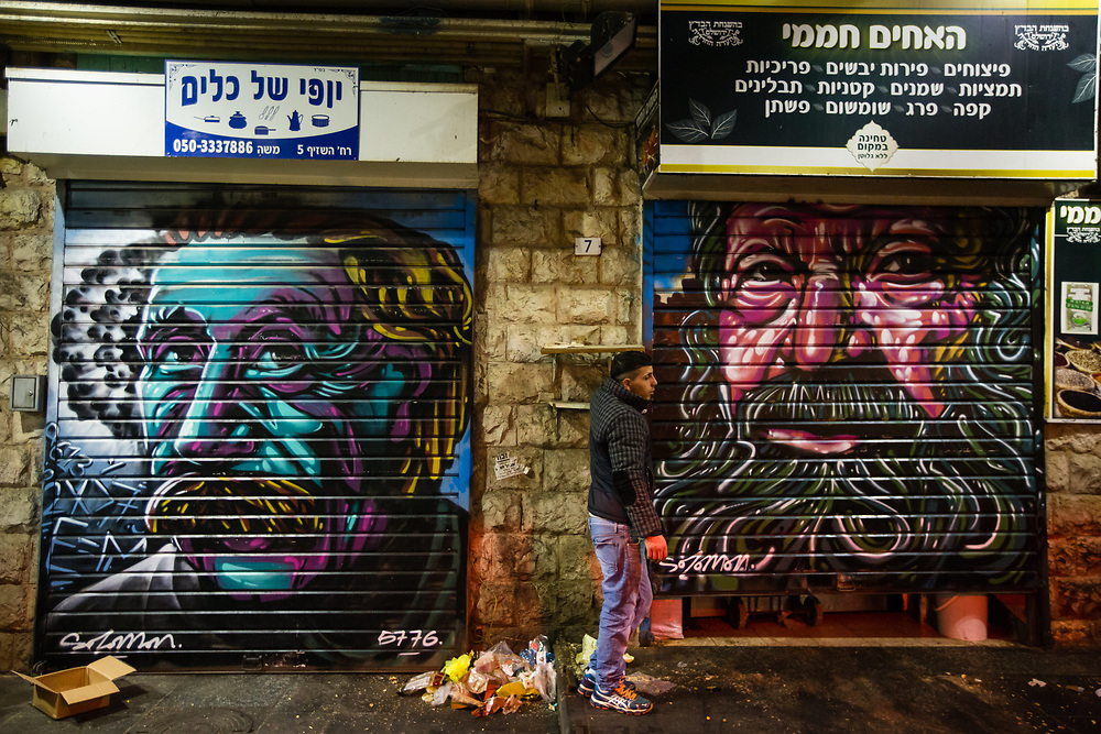 A vendor pulls down the shutter to a store next to graffiti depicting physicist Albert Einstein (L) which was painted over a closed shutter of another store at the Mahane Yehuda Market, often called 'The Shuk' in Jerusalem, Israel, on February 24, 2016.