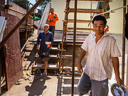 """15 FEBRUARY 2019 - SIHANOUKVILLE, CAMBODIA:  Chinese construction workers in Sihanoukville walk through their housing area on the way to lunch. The workers live in prefabbed units made in China and stacked atop each other like shipping containers. There are about 80 Chinese casinos and resort hotels open in Sihanoukville and dozens more under construction. The casinos are changing the city, once a sleepy port on Southeast Asia's """"backpacker trail"""" into a booming city. The change is coming with a cost though. Many Cambodian residents of Sihanoukville  have lost their homes to make way for the casinos and the jobs are going to Chinese workers, brought in to build casinos and work in the casinos.      PHOTO BY JACK KURTZ"""