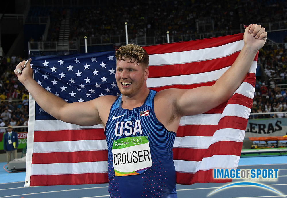 Aug 18, 2016; Rio de Janeiro, Brazil; Ryan Crouser (USA) poses with United States flag after winning the shot put in an Olympic record 73-10¾ (22.52m) during the 2016 Rio Olympics at Estadio Olimpico Joao Havelange.