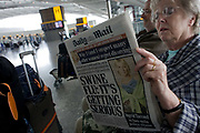 "Two elderly but travel-wise passengers read the morning newspapers while awaiting their check-in zone to open in Heathrow Airport's Terminal 5 departures concourse. The front page of the Daily Mail proclaims that Swine Flu is getting more serious after a period of summer when schools are about to re-open and temperatures about to drop for autumn. With their baggage stacked on a trolley the couple wait patiently after an early morning coach brought them to this aviation hub for BA only flights. From writer Alain de Botton's book project ""A Week at the Airport: A Heathrow Diary"" (2009)."