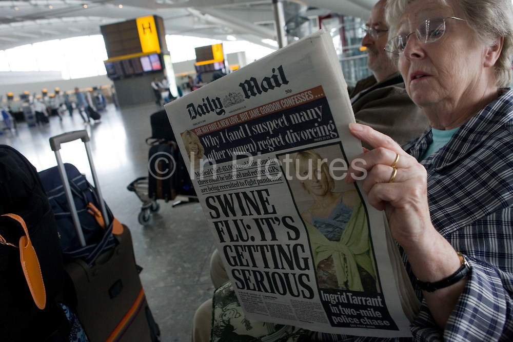 """Two elderly but travel-wise passengers read the morning newspapers while awaiting their check-in zone to open in Heathrow Airport's Terminal 5 departures concourse. The front page of the Daily Mail proclaims that Swine Flu is getting more serious after a period of summer when schools are about to re-open and temperatures about to drop for autumn. With their baggage stacked on a trolley the couple wait patiently after an early morning coach brought them to this aviation hub for BA only flights. From writer Alain de Botton's book project """"A Week at the Airport: A Heathrow Diary"""" (2009)."""
