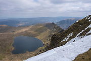 Red Tarn lake high up on the eastern flank of Helvellyn Mountain, English Lake District, Cumbria, UK.  Red Tarn is a glacial lake formed with the glacier that carved our the eastern side of the mountain melted. It is the habitat of the rare and endangered Schelly fish. It is a sunny day, but there is snow on the summit of the mountain.