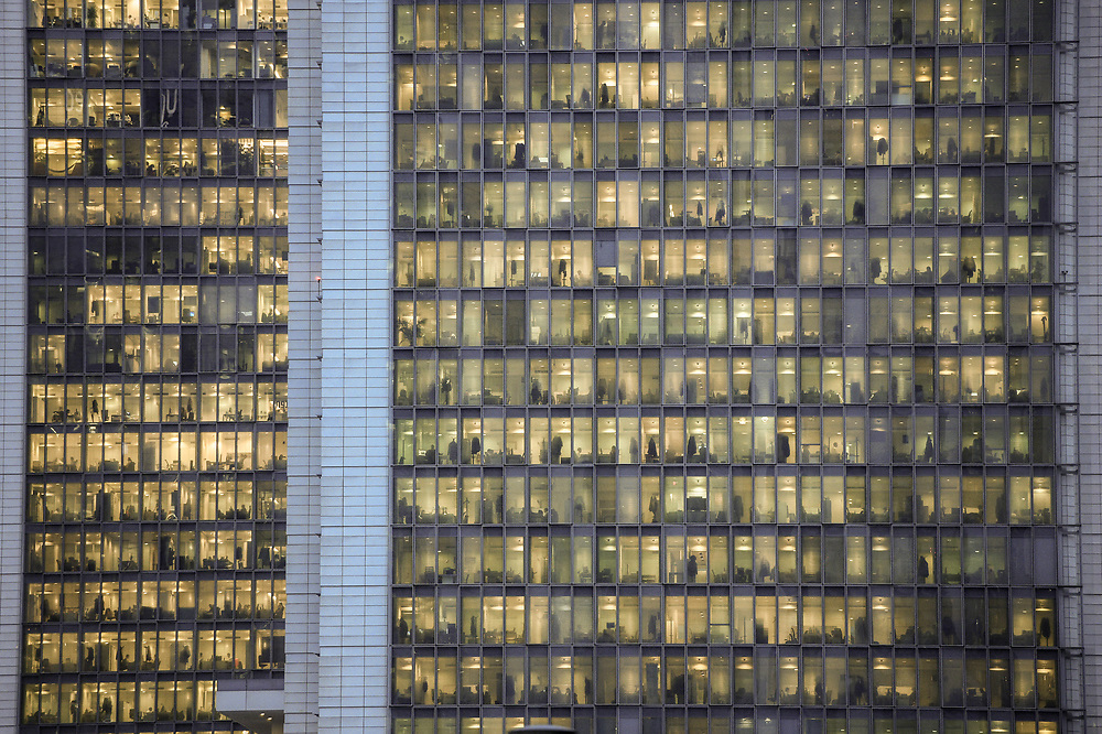 MILAN - NOV 8 -  view of a window with people working in the interior of an office building at night in Milan, Italy on November 8, 2018. Concept for employment, business, corporate, working, modern life