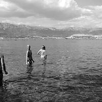 Swimmers in the water,<br />Beach & bay,<br />Marjan Park, walk and swiming,<br />Split, Croatia. 2018