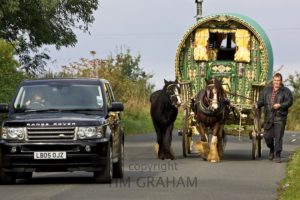 Range Rover car overtakes shire horse-drawn gypsy caravan on country lane, Stow-On-The-Wold, Gloucestershire, United Kingdom