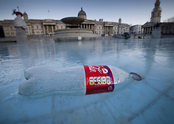 © Licensed to London News Pictures. 25/01/2021. London, UK. An empty plastic bottle is frozen in ice in the fountains in Trafalgar Square in central London as temperatures remain low. Yesterday saw the first snow of winter in the capital. Photo credit: Peter Macdiarmid/LNP