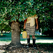 Man standing in holly tree holding watering sprayer can