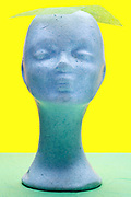styrofoam mannequin model face with a transparent green paper sheet on top of the head