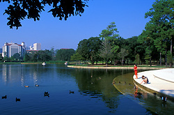 Stock photo of two girls feeding ducks at the pond in Hermann Park