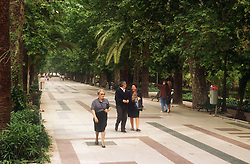 Paseo del Parque; Malaga; with people walking past trees,