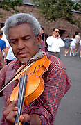 African American street musician age 55 playing violin in city park.  New York  New York USA