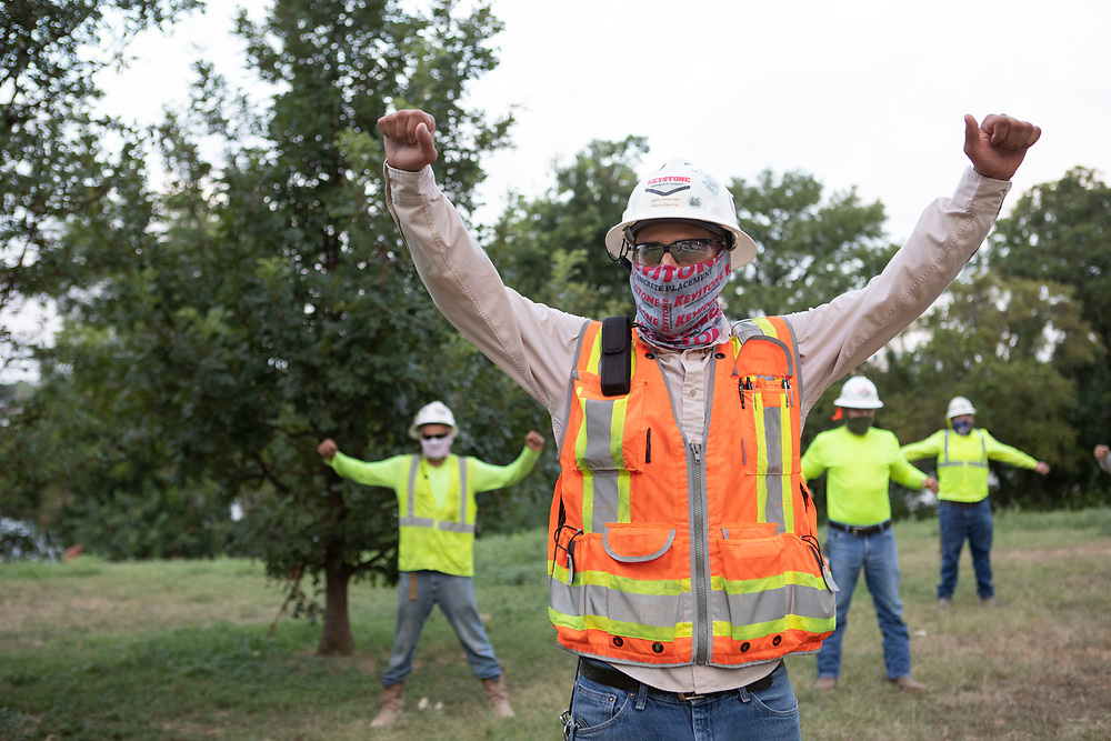 Austin, TX USA July 14, 2020: Construction workers listen to safety briefings and do a short exercise program as they prepare for an eight-hour shift in the 105-degree Texas heat.  Crews are on the second story of a planned 53-story building as they take precautions against the coronavirus pandemic.