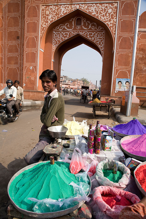 Boy selling coloured paint powder from a cart during Holi festival in Jaipur, Rajasthan, India