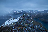 Female hiker takes in view of mountain landscape from summit of Narvtind mountain peak, Moskenesøy, Lofoten Islands, Norway