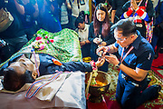 27 JANUARY 2014 - BANGKOK, THAILAND:  A man pours water into hand of Suthin Taratin during the bathing rites for the anti-government leader at Wat Sommanat Rajavaravihara in Bangkok. In Thai tradition, after death a bathing ceremony takes place in which relatives and friends pour water over one hand of the deceased. Suthin was a core leader of the People's Democratic Force to Overthrow Thaksinism (Pefot), one of several organizations leading protests against the elected government of Thai Prime Minister Yingluck Shinawatra. He was murdered Sunday, Jan. 28, while he was leading a rally to prevent voters from reaching a polling center in the Bang Na district of Bangkok.    PHOTO BY JACK KURTZ
