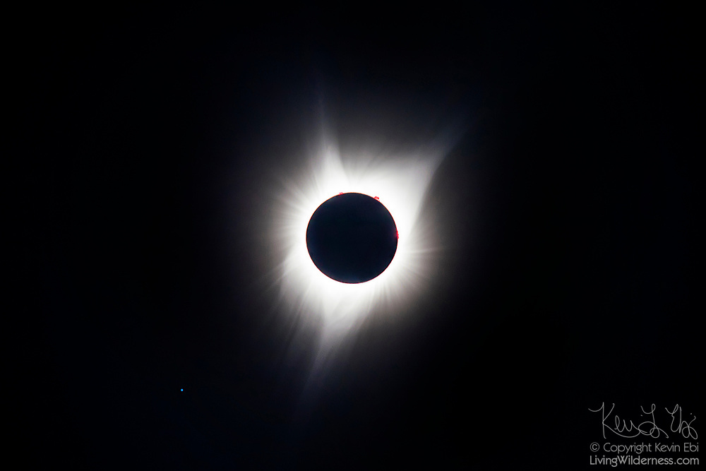 The sun's corona is visible to the naked eye during the total solar eclipse of August 21, 2017, as viewed from Malheur County, Oregon. The corona is an extremely hot plasma aura — as much as 450 times the temperature of the sun's surface — that extends millions of miles out from the solar disk that is typically visible. The sun's surface is far brighter than the corona, usually outshining it. During a total solar eclipse when the moon blocks the view of the main body of the sun, the corona becomes visible. The bright star Regulus is visible near the bottom left corner of the image.