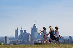 Three women enjoy the sunshine on Parliament Hill on another hot day in London. London, July 03 2018.