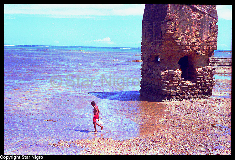 Young Fisherman by Star Nigro<br /> <br /> This moment was captured on an island off of the coast of Bahia,Brazil. This child fishing added a lively addition to this otherwise mysterious ruin on the beach.<br /> <br /> <br /> © 2021  All artwork is the property of STAR NIGRO.  Reproduction is strictly prohibited.