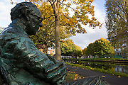 Bronze statue of Irish poet Patrick Kavanagh on the Grand Canal, Dublin, by sculptor John Coll.... ..Canal Bank Walk.  ..  .Leafy-with-love banks and the green waters of the canal.Pouring redemption for me, that I do.The will of God, wallow in the habitual, the banal,.Grow with nature again as before I grew..The bright stick trapped, the breeze adding a third.Party to the couple kissing on an old seat,.And a bird gathering materials for the nest for the Word.Eloquently new and abandoned to its delirious beat..O unworn world enrapture me, encapture me in a web.Of fabulous grass and eternal voices by a beech,.Feed the gaping need of my senses, give me ad lib.To pray unselfconsciously with overflowing speech.For this soul needs to be honoured with a new dress woven.From green and blue things and arguments that cannot be proven..