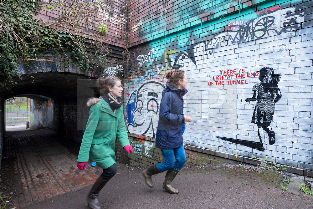 """© Licensed to London News Pictures; 14/03/2021; Bristol, UK. People walk past a mural in the style of Banksy with an image of a girl and with the words """"There is light at the end of the tunnel"""", is seen next to a tunnel under the railway off Muller Road in Bristol. According to some locals it has been painted very recently, perhaps early this morning. Banksy often comments on current events, and if the piece is by Banksy it could be a reference to the end of the covid-19 coronavirus pandemic, or to social movements such as #MeToo, Black Lives Matter, or Reclaim the Streets. Photo credit: Simon Chapman/LNP."""